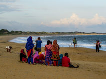 Srilankan people on the beach. View of the long beach in Yala National Park, with Srilankan people, with their typical colorful dresses stock image