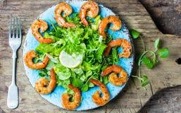 Srimp lettuce salad on blue plate, wooden rustic background Stock Image