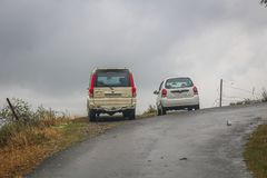 Srinagar, Jammu and Kashmir, India: Dated- March 20, 2019- A Mahindra Scorpio and a Maruti Suzuki Alto parked on the side of a. Hilly road in Kashmir stock photography
