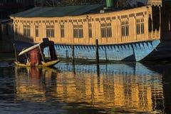 Srinagar Kashmir Houseboat. Small shikara transport boat passing a houseboat on Dal Lake at sunset, Srinagar, Kashmir, India Royalty Free Stock Photo