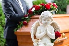 Sörjande man på begravningen med kistan Fotografering för Bildbyråer