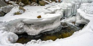Sroga zimna zima minus z temperaturami rozwija malownicze lodowe formacje na skałach w wartko biega zatoczce zdjęcia royalty free