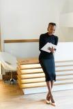 Srogo elegancka biznesowa kobieta jest ubranym czerń beżu i sukni buty w lekki biurowym patrzejący jej agendę, pełny długość port Zdjęcia Royalty Free