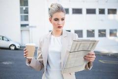 Srogo eleganckiego bizneswomanu czytelnicza gazeta Obraz Royalty Free