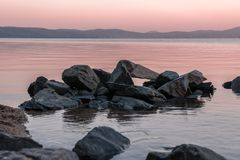 Pink sunrise at Turgoyak lake. Srones in the water of mountain lake in the morning Royalty Free Stock Photo