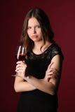 Srta. con el vino y los brazos cruzados Cierre para arriba Fondo rojo oscuro Imagenes de archivo
