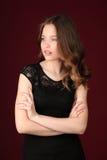 Srta. con los brazos cruzados Cierre para arriba Fondo rojo oscuro Imagen de archivo libre de regalías