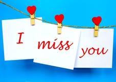 Srta. que usted manda un SMS en las etiquetas engomadas que cuelgan en los pernos de la forma del corazón Imagenes de archivo