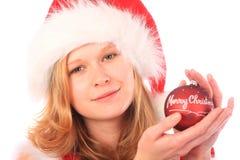 Srta. Santa está sosteniendo una bola roja del árbol de navidad Foto de archivo libre de regalías
