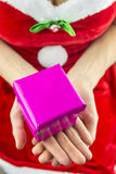 Srta. santa que lleva a cabo el regalo de Navidad Imagen de archivo libre de regalías