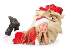 Srta. santa que miente al lado de la sonrisa del saco de la Navidad Imágenes de archivo libres de regalías