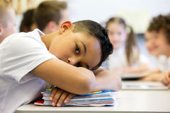 Sruggling At School. A close up shot of a little boy at school who looks distant and upset Royalty Free Stock Image