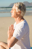 Ssenior man with eyes closed meditating at beach during sunny day Royalty Free Stock Photos