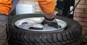 Sservice man put on tyre on car wheel by special tool, mechanic using mounting tool for tire repair