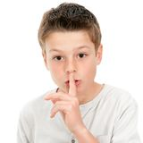 Ssh! Silence please. Cllose up portrait of boy with finger on lip demanding silence .isolated on white background royalty free stock images