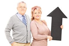 Ssmiling mature couple holding a big black arrow pointing up Royalty Free Stock Photography