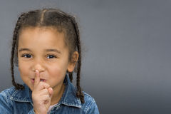 Ssshhh!. A beautiful mixed race girl with her finger to her lips and laughing Royalty Free Stock Photography