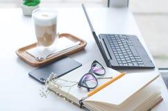 Stół w jaskrawej kawiarni z latte i freelancer pracy szczegółami fotografia stock