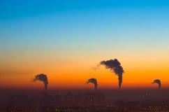 Städer och industriella rökmoln himmelsolnedgången Royaltyfri Foto