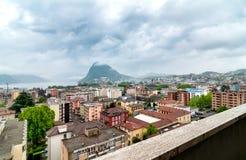 Städtische Ansicht von Lugano mit Monte Bre im Nebel lizenzfreie stockbilder