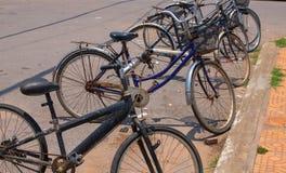 Städtische Fahrräder geparkt durch Straße Rustikales altes bibycles Parken Asiatische Straßenansicht mit populärem Transport Stockfotografie