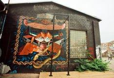 Städtische Grafik durch unbekannten Künstler auf verlassener Hausstraße mit Graffiti Stockfotografie