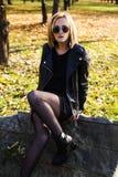 Städtische Jugendliche mit der Sonnenbrille, die in einer Lederjacke aufwirft Stockbilder