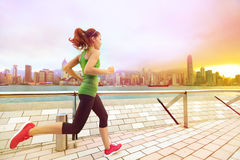 Städtische Läuferfrau, die in Hong Kong bei Sonnenuntergang rüttelt Stockfotografie