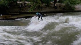 Städtische Surfer reiten die stehende Welle auf den Eisbach-Fluss, München, Deutschland stock video