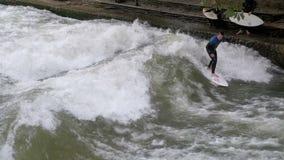 Städtische Surfer reiten die stehende Welle auf den Eisbach-Fluss, München, Deutschland Langsame Bewegung stock video