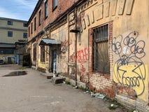 Städtische Szene des Schmutzes mit Tür und Graffiti stockfotografie