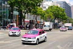 Städtische Szene mit traditionellen rosa Taxis in im Stadtzentrum gelegenem Mexiko City stockbild