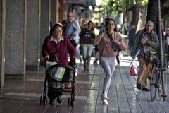 Städtische Szene: Ungültige Dame und eine schnelle junge Frau Stockfotos