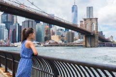 Städtische touristische Frau New York City, die Brooklyn-Brücke und Skyline betrachtet stockfotos