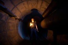 Städtischer Forscher mit Kerze in der Untertagekommunikations-, Heizungshauptleitung, im Abwasserkanaltunnel, in usw. Stockfotografie
