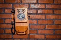 Städtischer Hintergrund des Schmutzes einer Backsteinmauer mit einem alten Münztelefon außer Dienst Stockbilder