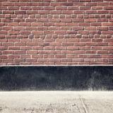 Städtischer Hintergrund mit Backsteinmauer und Pflasterung Lizenzfreies Stockfoto