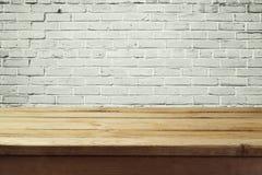 Städtischer Hintergrund mit leerem Holztisch und Backsteinmauer Stockfotografie