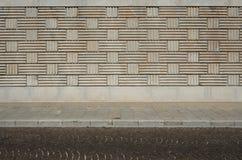 Städtischer Hintergrund Wand mit geometrischen Mustern, Bürgersteig und Straße mit Porphyrwürfeln stockfotografie