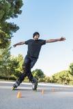 Städtischer junger Mann auf Rollschuhen auf der Straße zur Sommerzeit lizenzfreie stockfotos