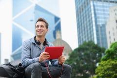 Städtischer Mann auf der Tablette, die in Hong Kong sitzt Stockfotos