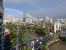 Städtischer Regenbogen über dem Fluss Stockbild
