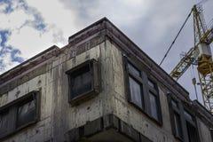 Städtisches konkretes Gebäude, das mit Kran im backgr erneuert wird Stockbilder
