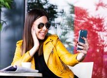 Städtisches Mädchen sitzen in Café nehmendem selfie im Freien lizenzfreie stockbilder