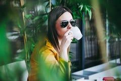 Städtisches Mädchen sitzen im trinkenden Kaffee des Cafés im Freien lizenzfreies stockfoto