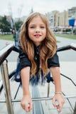 Städtisches Modeporträt einer Jugendlichen in der Straße am Geländer auf der Treppe Stockbild