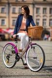 Städtisches Radfahren - Mittelalterfrau und -fahrrad in der Stadt Stockfoto