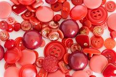 Ställ in av att sy röd färg för knappar Bakgrund arkivfoto