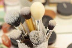 Ställ in av borstar i ett exponeringsglas för att applicera makeup hjälpmedel- och fast tillbehörmakeupkonstnär royaltyfria bilder