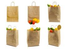 Ställ in av brun pappers- påse med grönsaker Återanvänd packe med ny organisk mat som isoleras på vit bakgrund arkivfoto